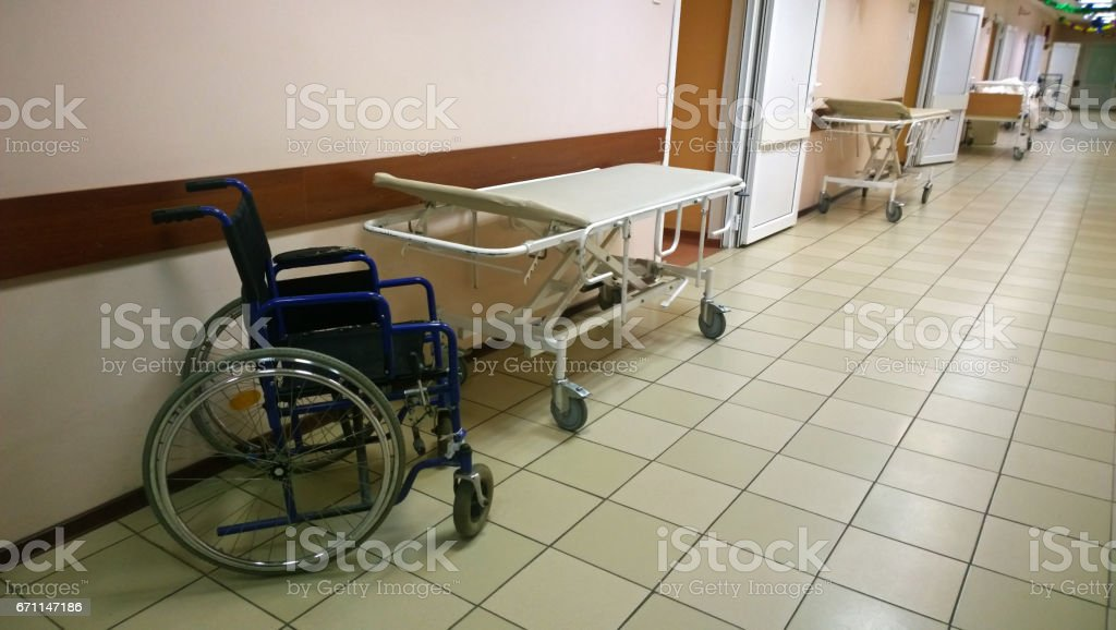 Bright, clean hallway in a medical facility - along the walls are medical bed and wheelchair stock photo