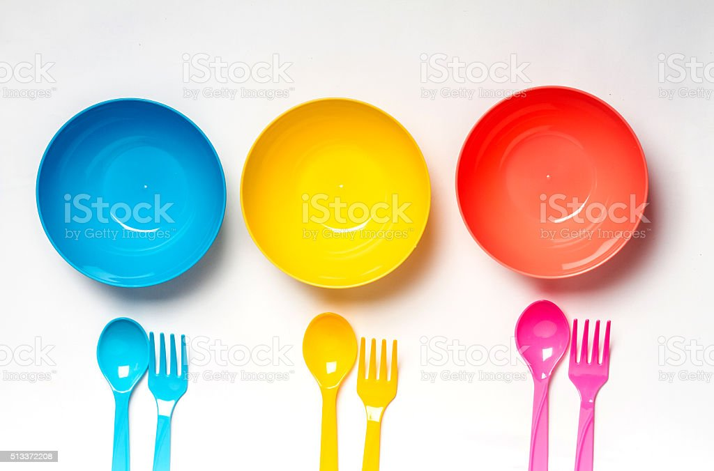 Bright colorful plastic disposable tableware on white background stock photo