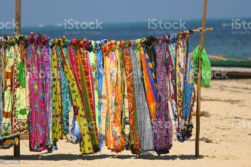 Bright, colorful scarves hanging from pole on a beach stock photo