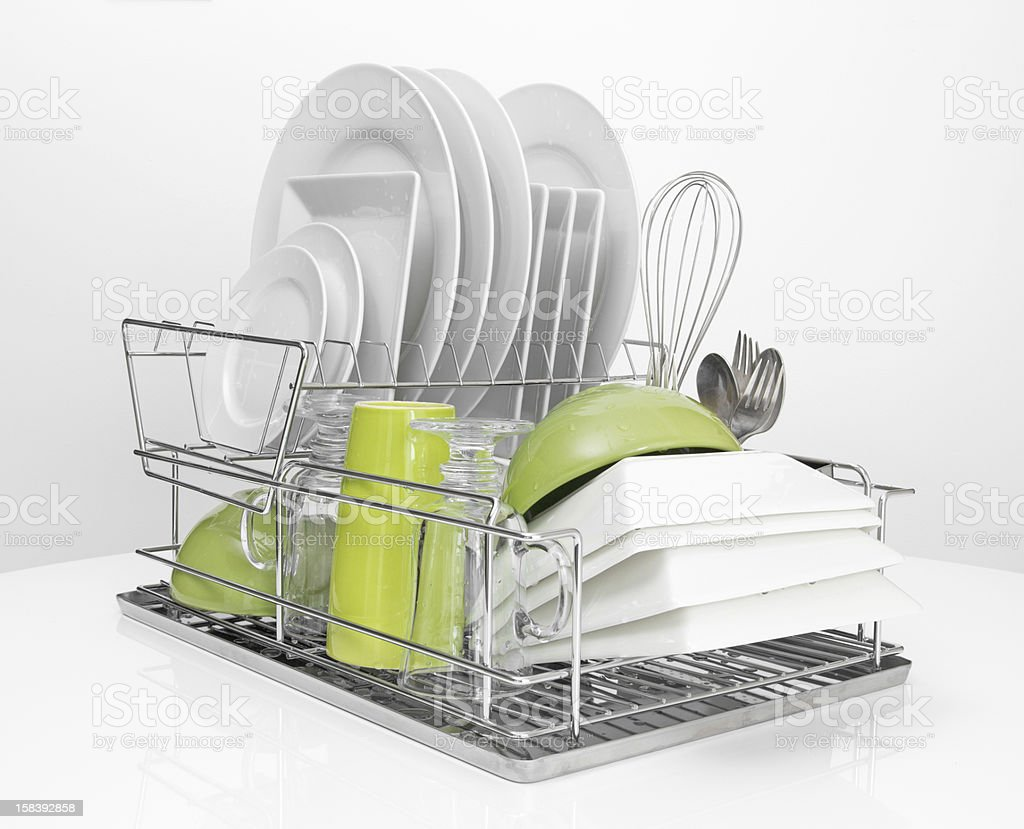 Bright dishes drying on metal dish rack stock photo