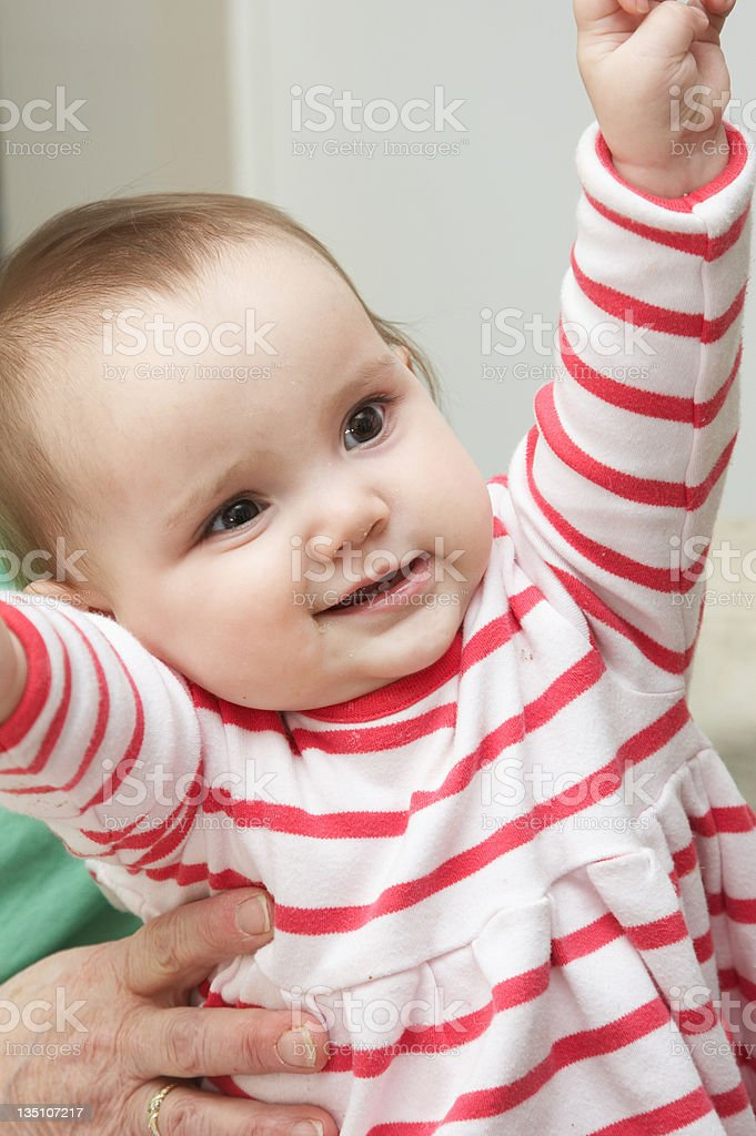 Bright eyed one year old girl arms up stock photo