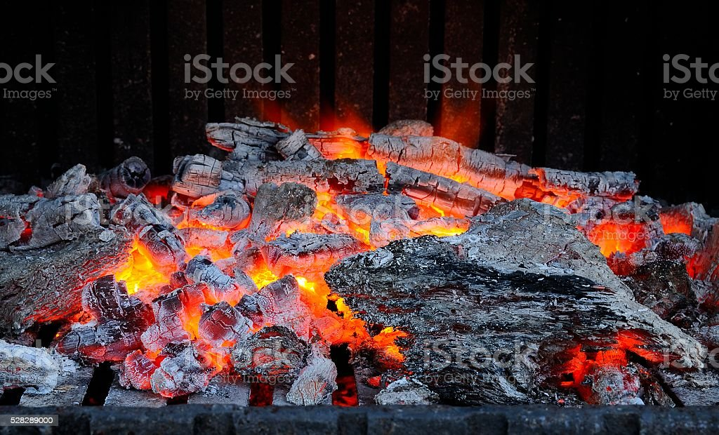 Bright flame in ashy firewoods stock photo