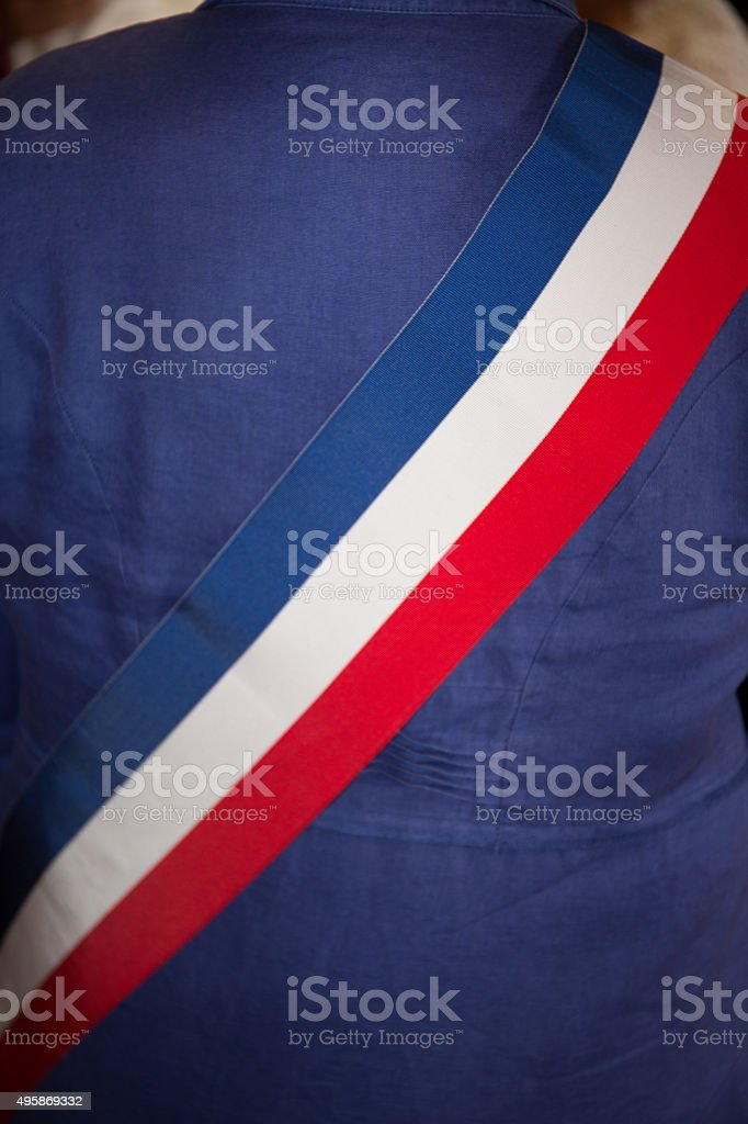 Bright French Mayor scarf under blue jacket stock photo