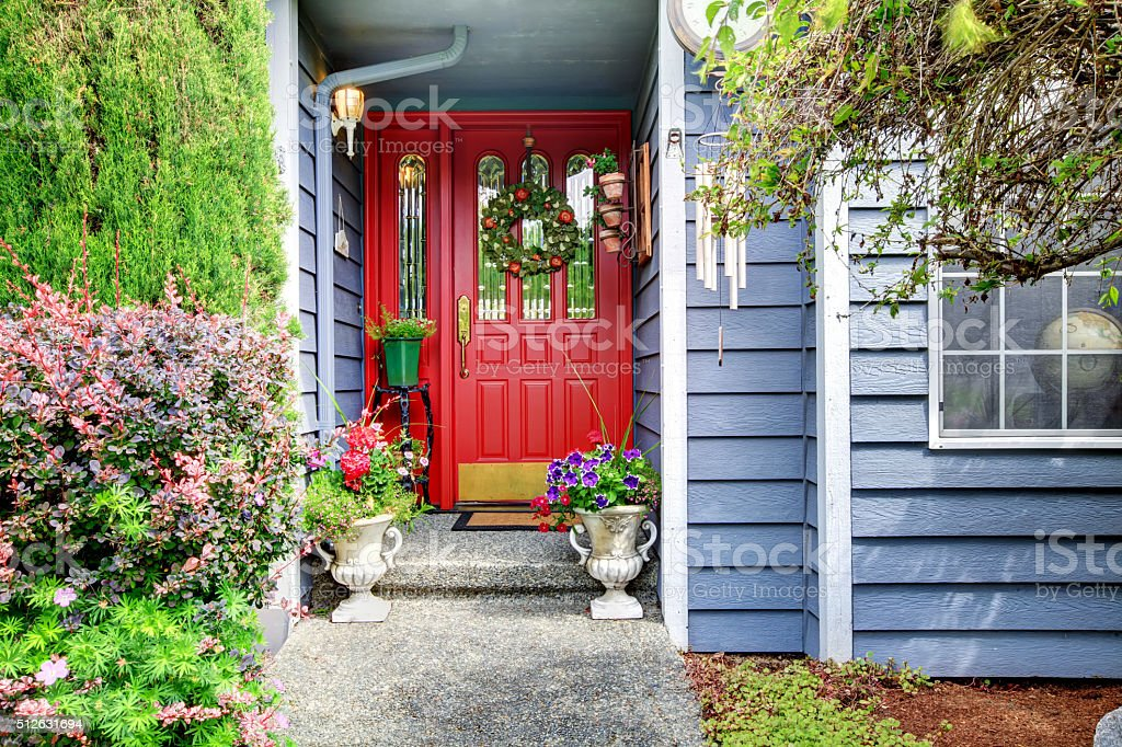 Bright front red door to blue American home. stock photo