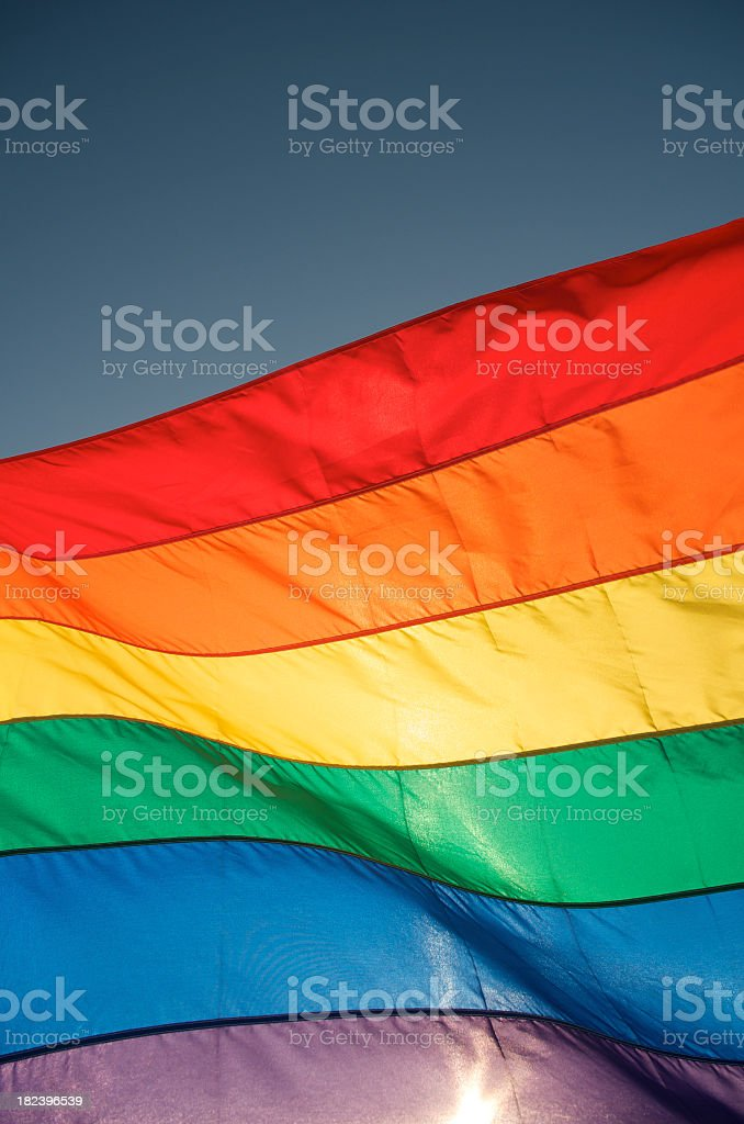Bright Gay Pride Rainbow Flag Waves in Blue Sky Sun stock photo