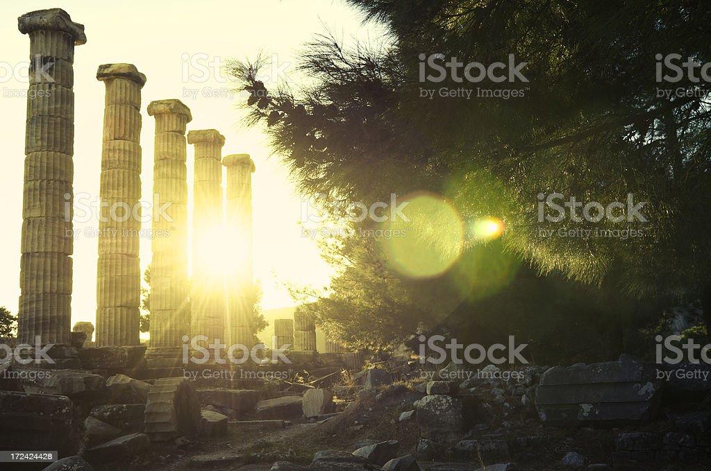 Bright Golden Sun Shines Behind Ancient Greek Columns royalty-free stock photo