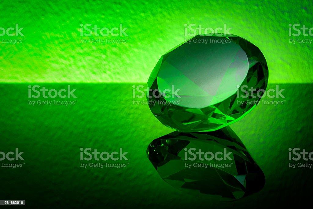 Bright green emerald on a shiny table stock photo