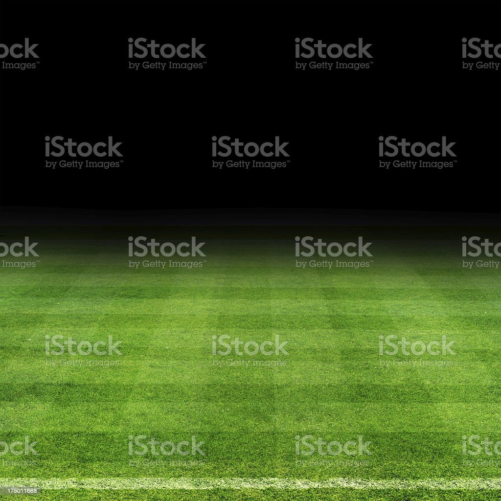 Bright green football field under a dark sky stock photo