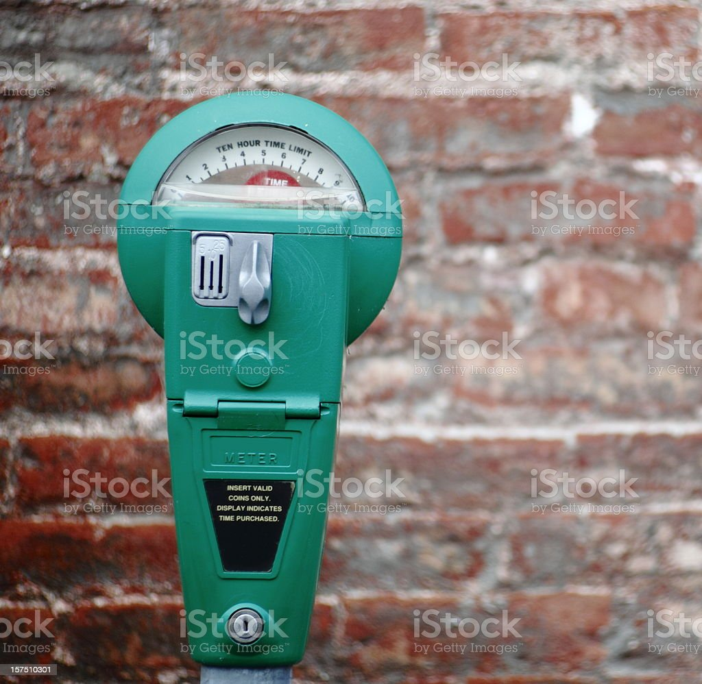 A bright green parking meter on a brick background stock photo