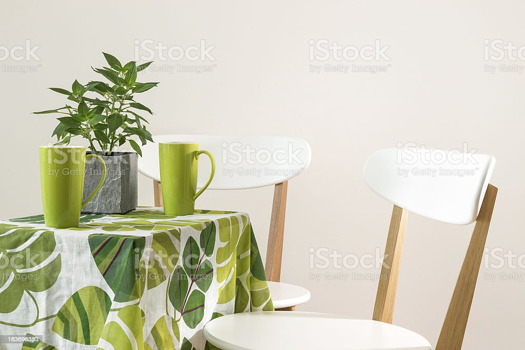 Bright green table with teacups royalty-free stock photo