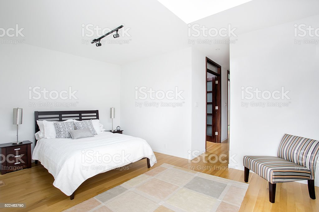 Bright Guest bedroom with easy chair. stock photo