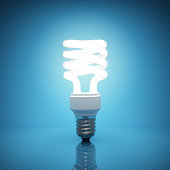 Bright, illuminated light bulb on blue background