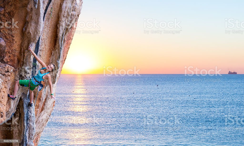 Bright Image of Young Rock Climber Sunrise and Ocean Background stock photo