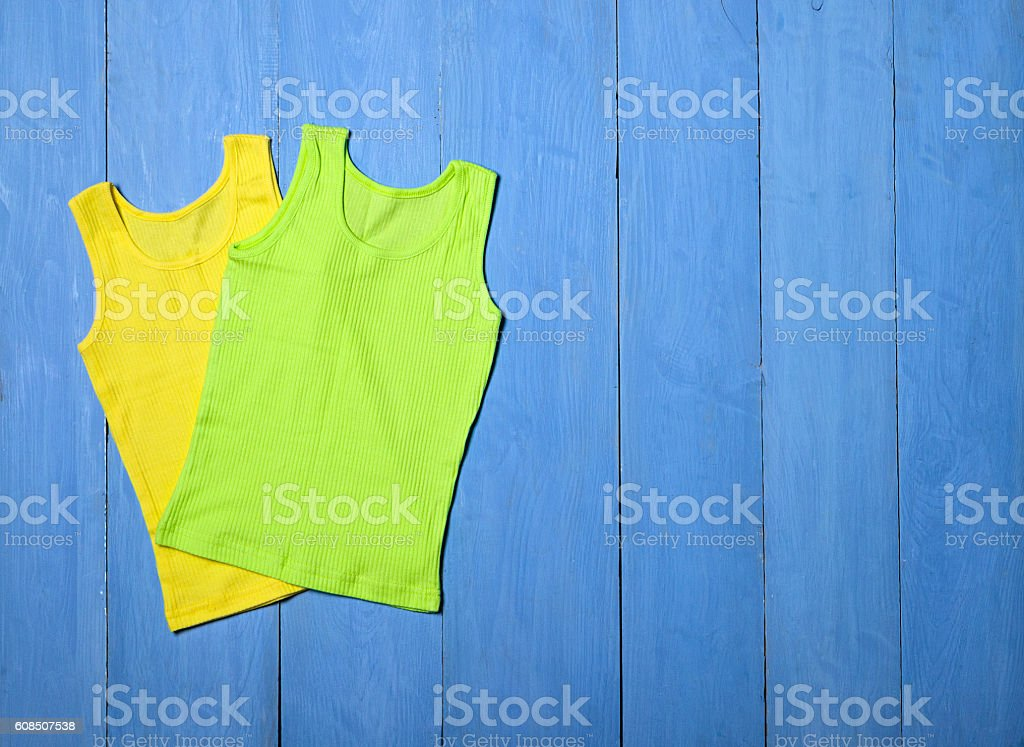 bright knitted T-shirt on blue wooden background stock photo