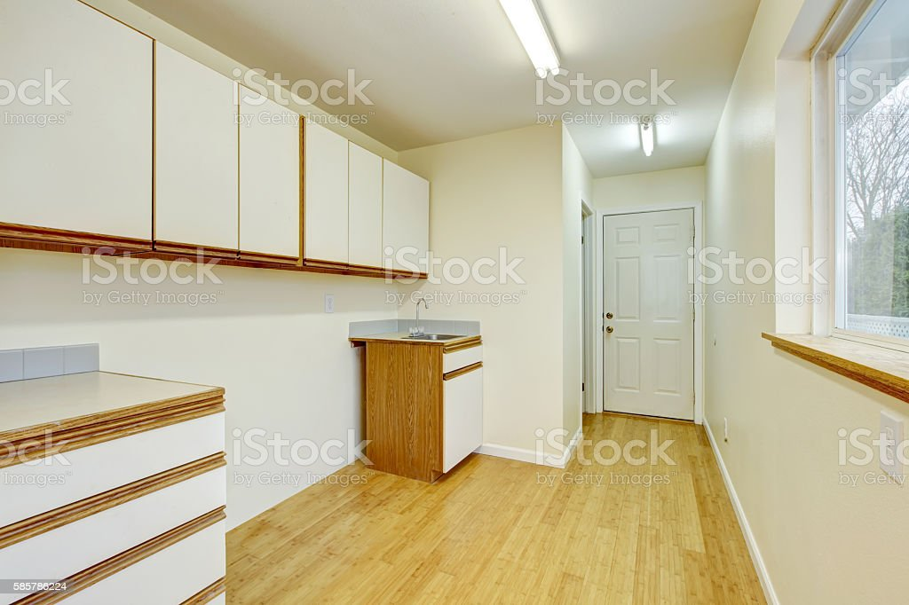 Bright laundry room interior with cabinets and hardwood flooring. stock photo