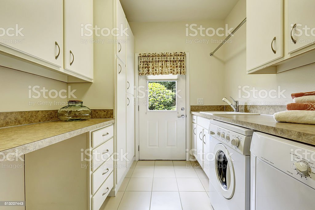 Bright laundry room with white cabinets stock photo