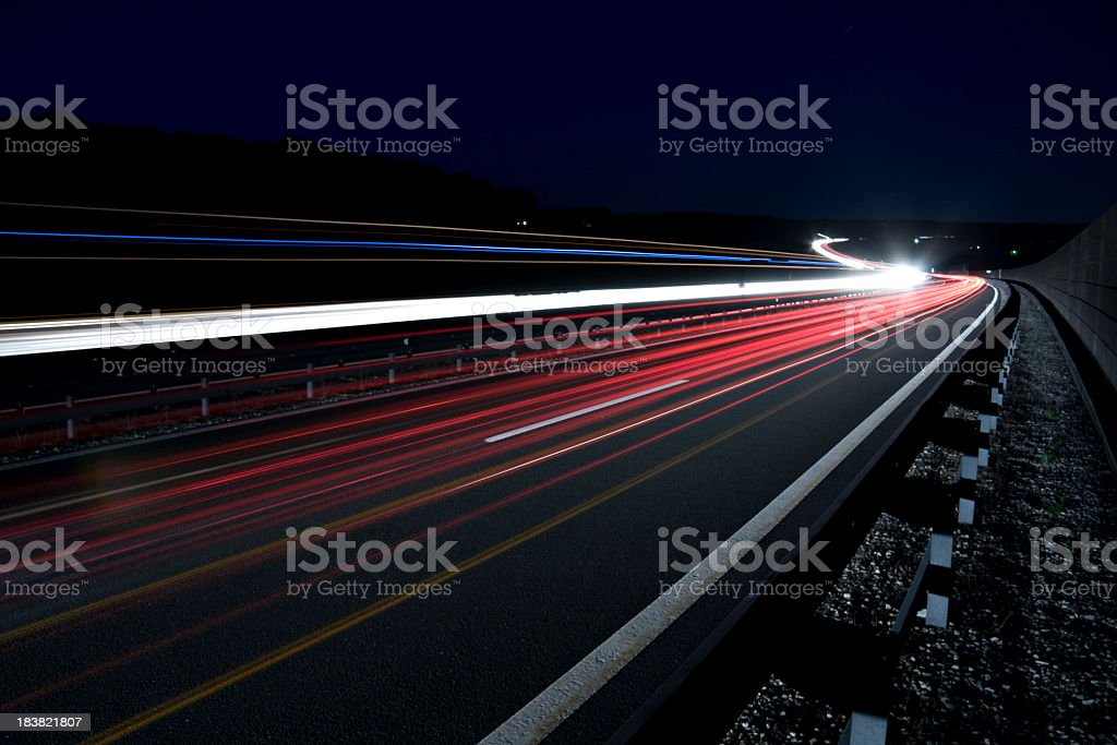 Bright light trails on the road in the dark stock photo