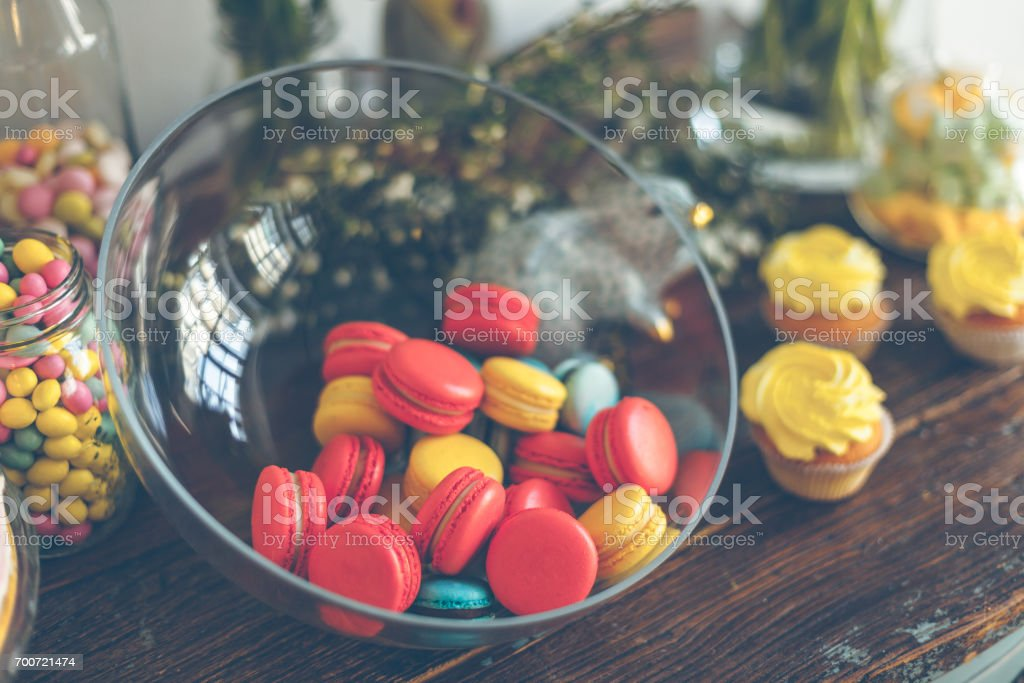Bright macaroons and cupcakes on a table stock photo