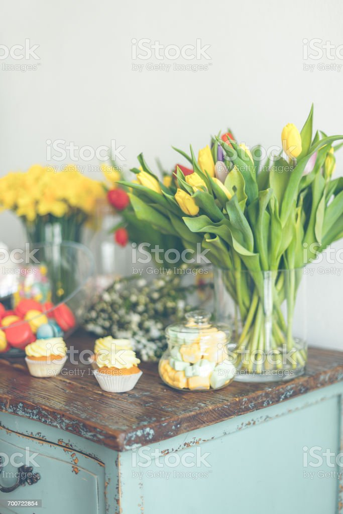 Bright macaroons and cupcakes on a wooden table stock photo