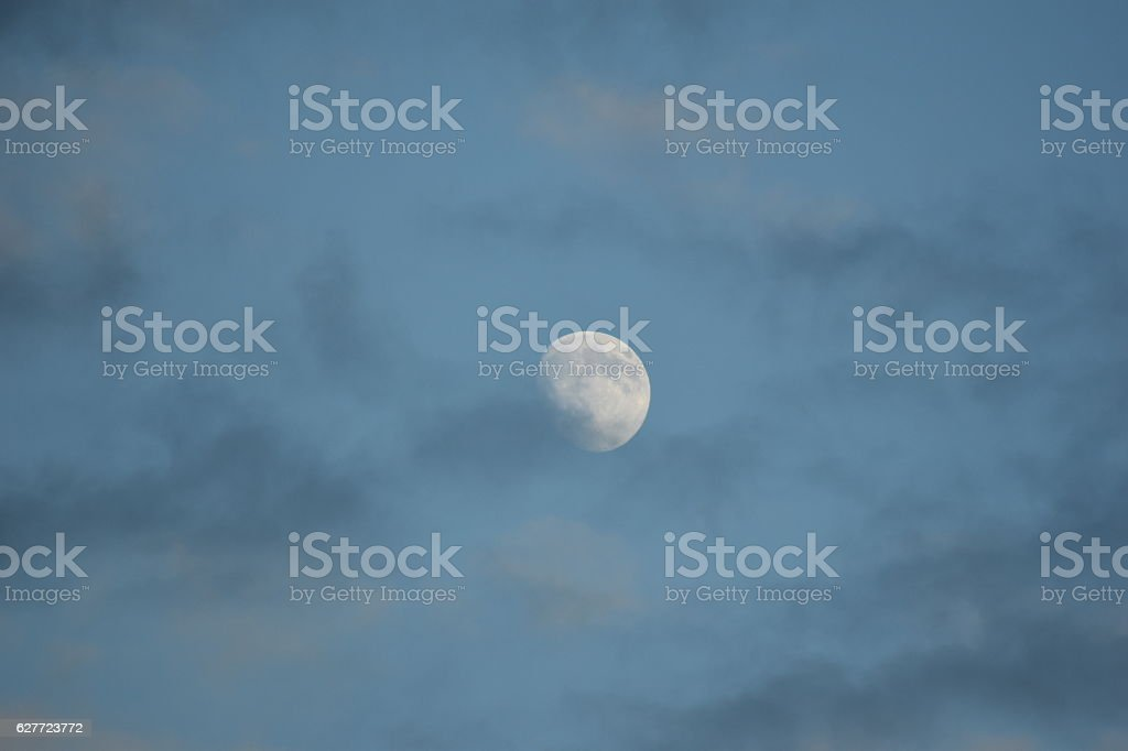 Bright Moon at Dusk Blue Sky Some Clouds stock photo