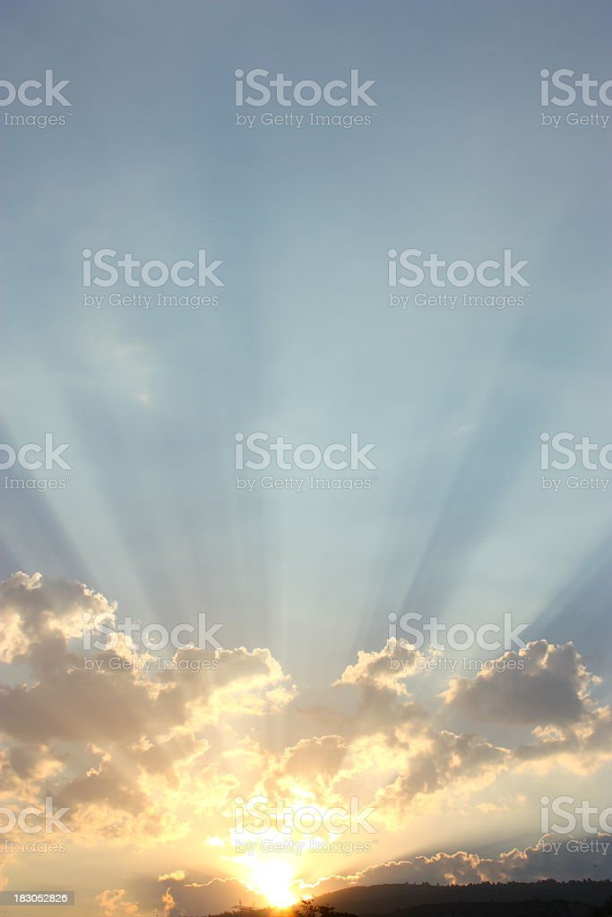 Bright morning sun rays peeking over clouds stock photo