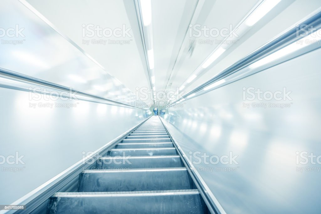 Bright motion blurred escalator, reflective metal stock photo