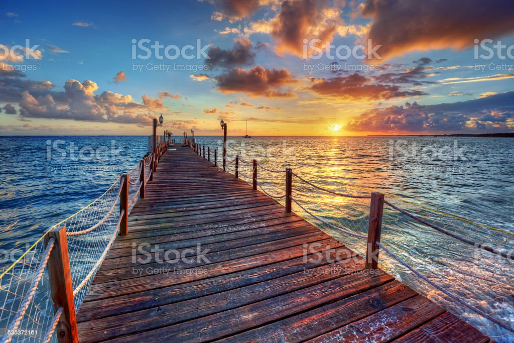 Bright ocean pier sunrise with colorful clouds over azure waters stock photo
