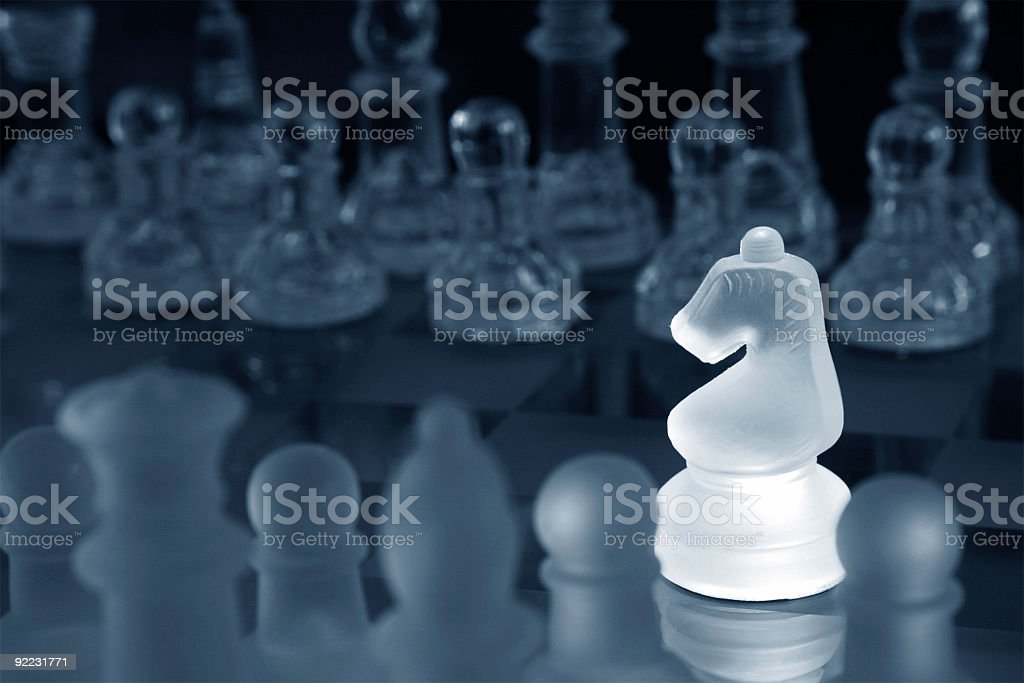 Bright opaque white knight among other dimmer chess pieces royalty-free stock photo