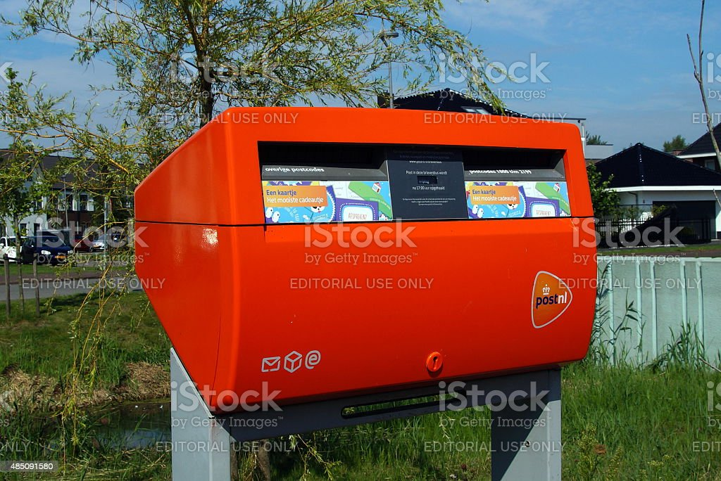 Bright orange Dutch PostNL mailbox stock photo