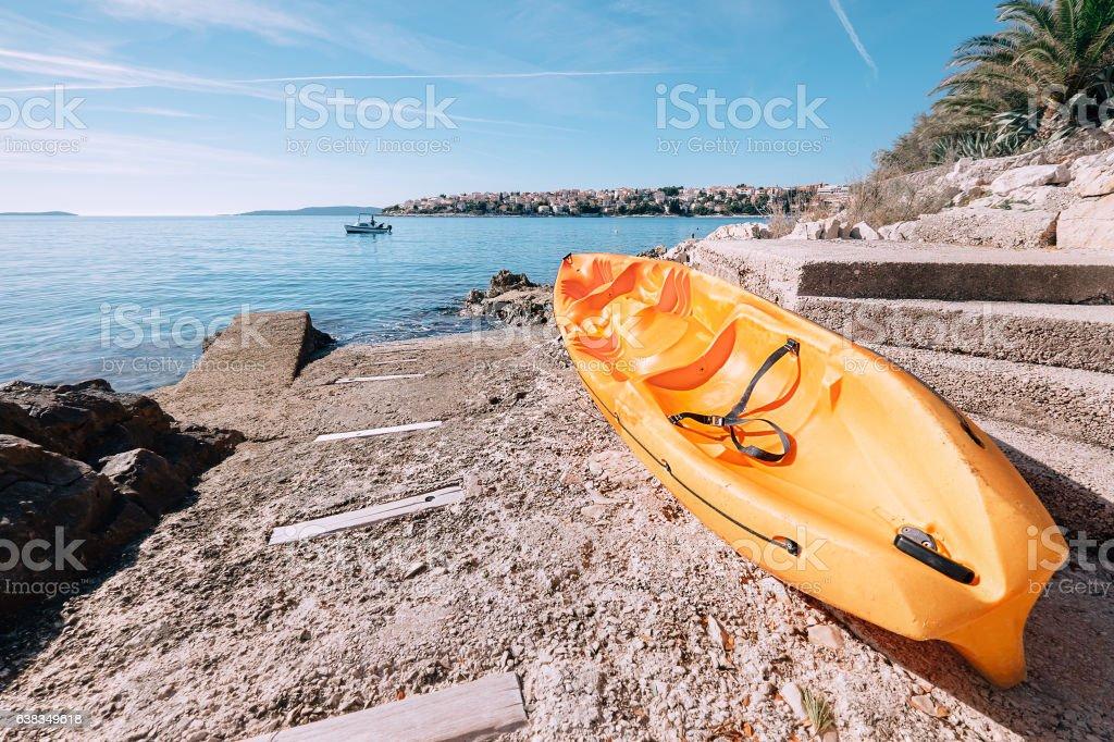 Bright orange kayak is on the sea pier stock photo