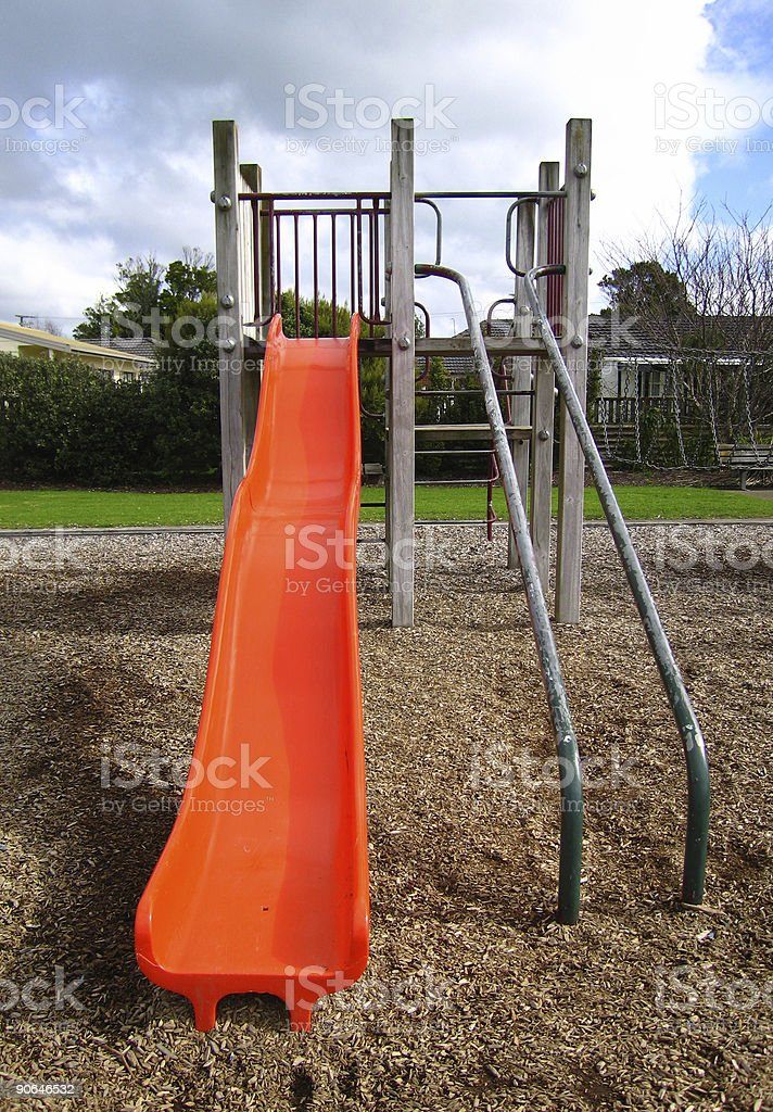 Bright orange slide in playground stock photo