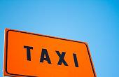 Bright Orange Taxi Sign, Blue Sky Background