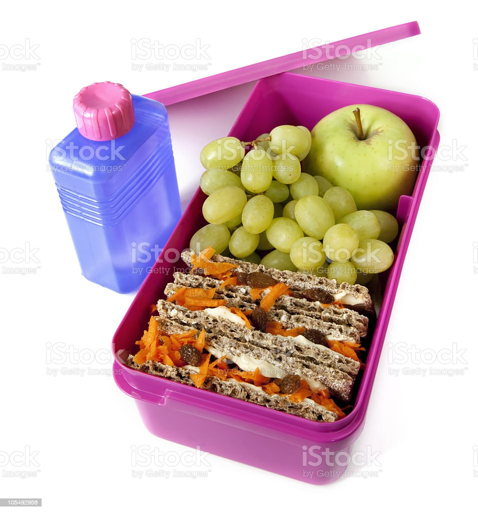 Bright pink lunchbox containing fruit and a healthy sandwich royalty-free stock photo