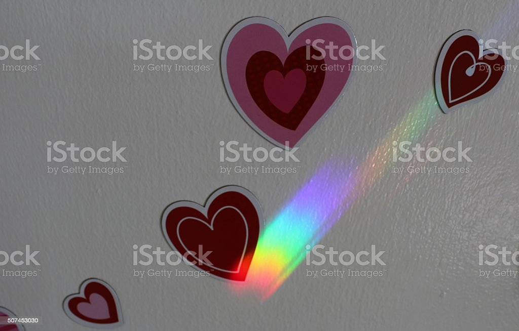 Bright Rainbow Colored Lights Connecting Two Hearts stock photo