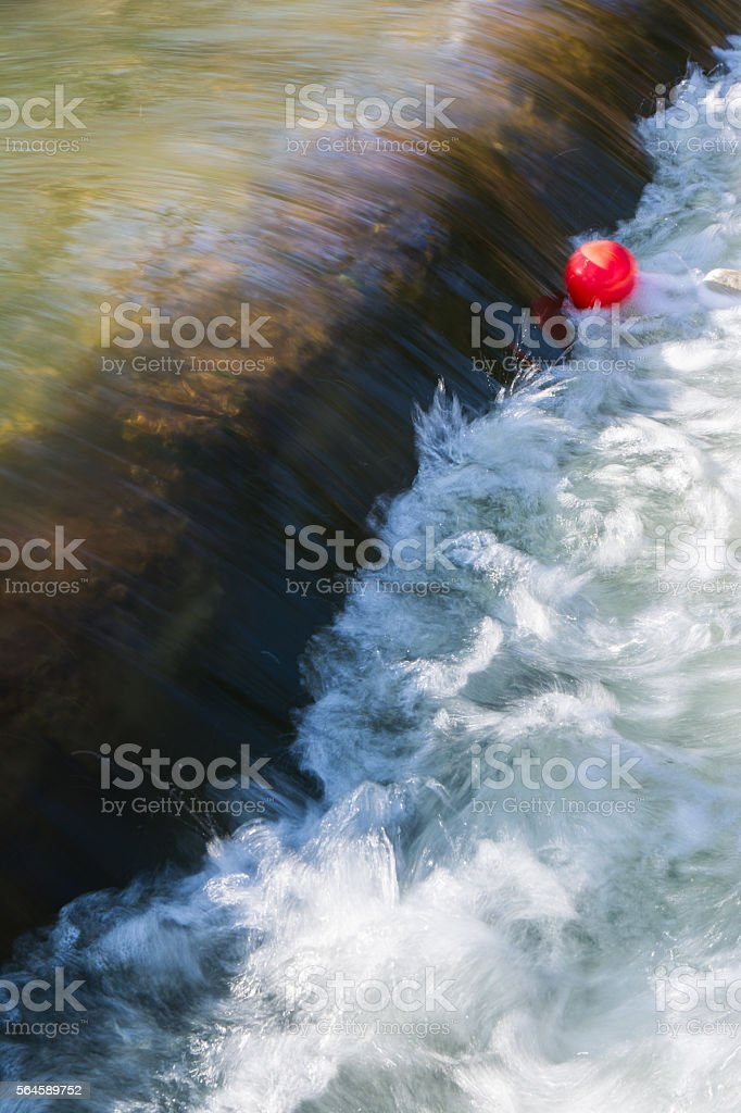 Bright Red Balloon Trapped in Flowing River stock photo