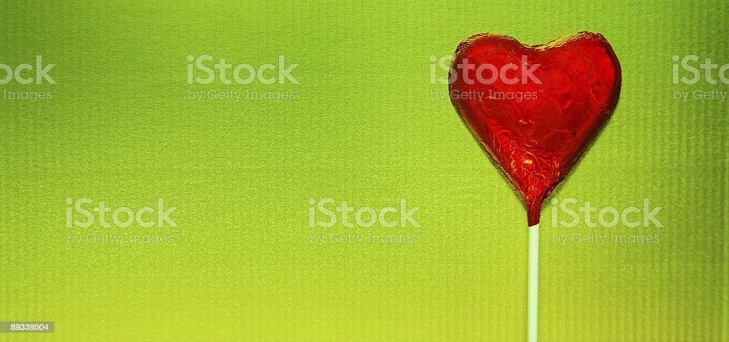 bright red chocolate heart on green background royalty-free stock photo