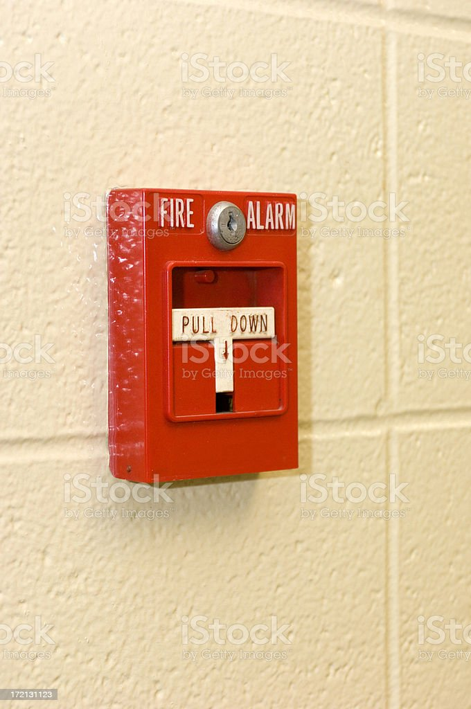 A bright red fire alarm on a concrete wall stock photo