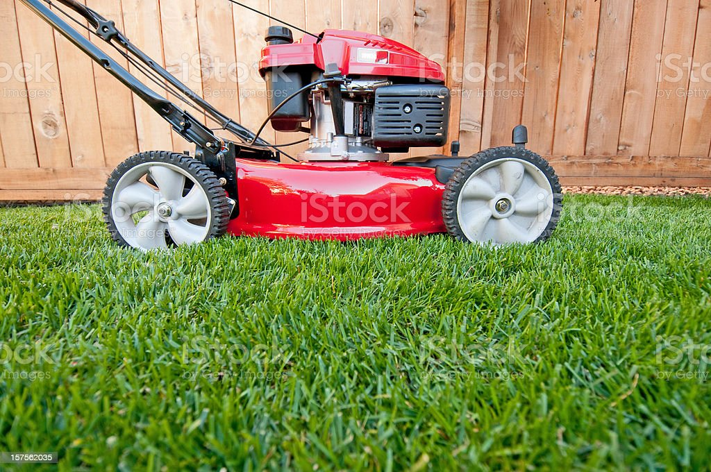 Bright red lawn mower ready for business stock photo