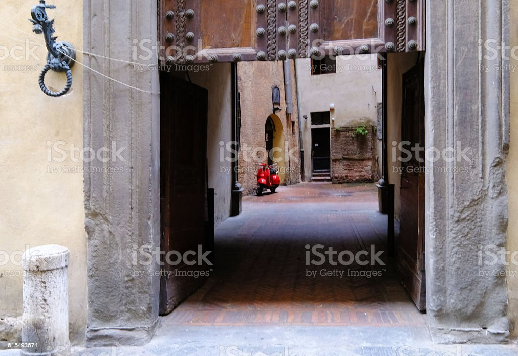 Bright Red Scooter in Italian Courtyard stock photo
