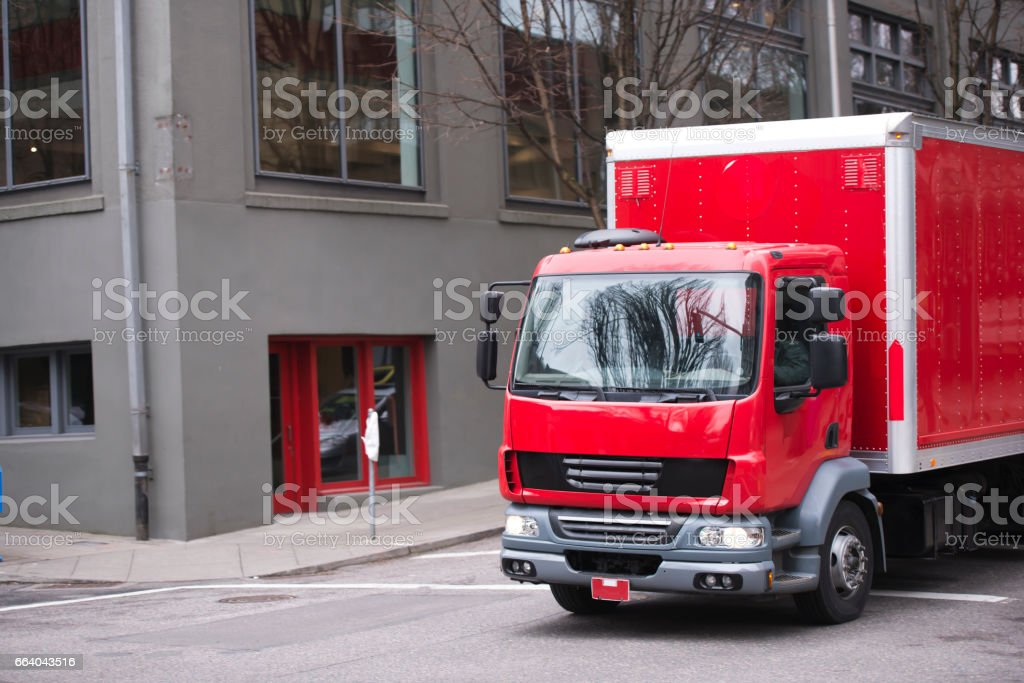 bright red small semi truck with box trailer going by urban city street stock photo