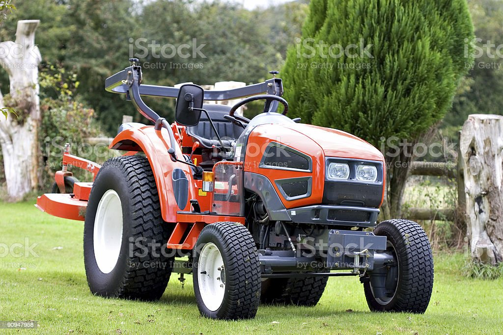 A bright red tractor on green grass stock photo