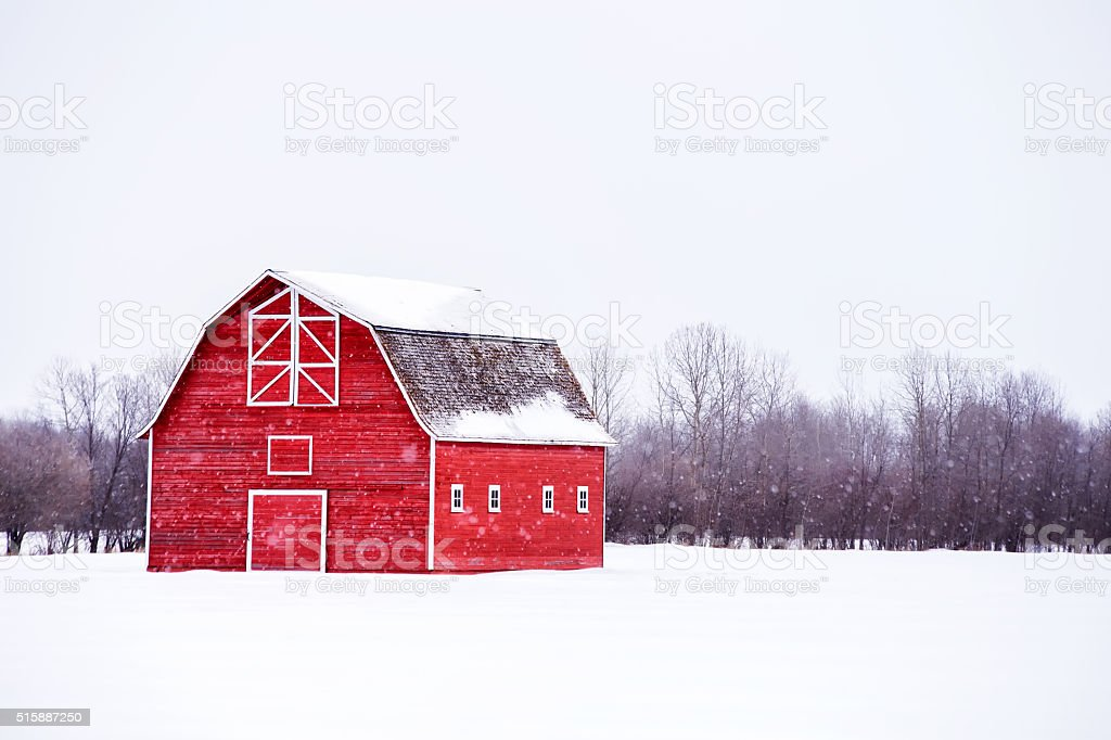 Bright red with hayloft in winter landscape stock photo