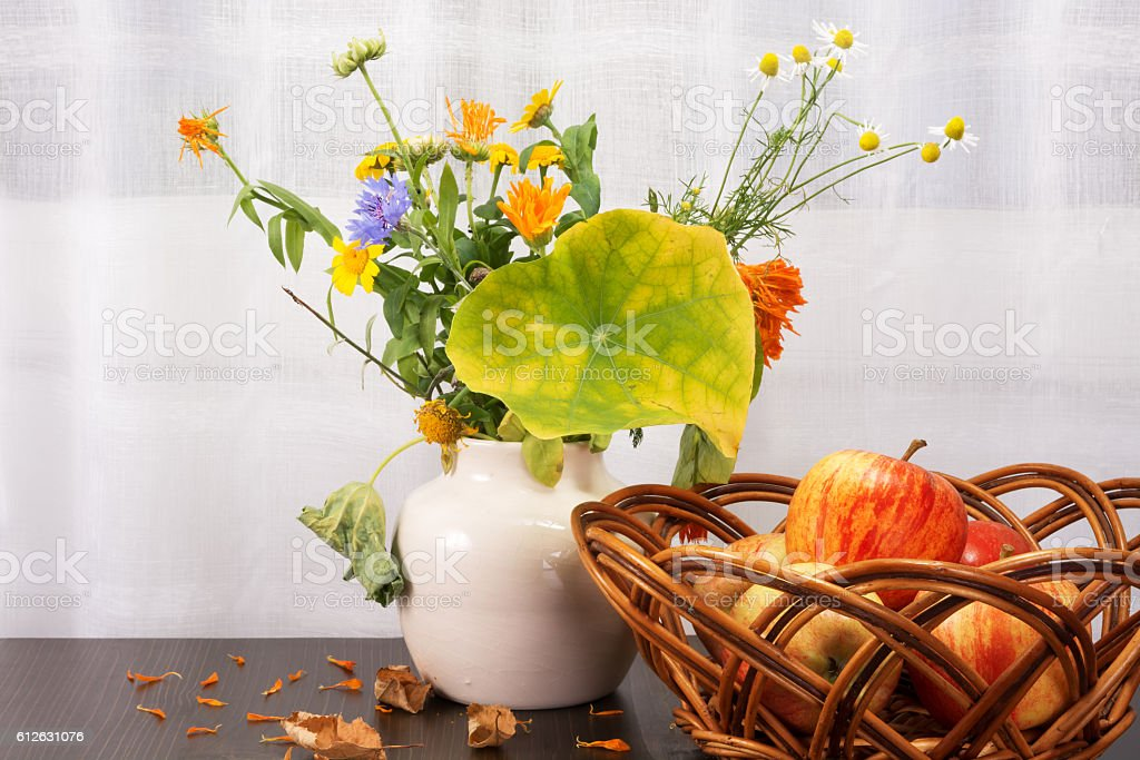 Bright rustic bouquet of flowers, apples in a wicker bowl stock photo