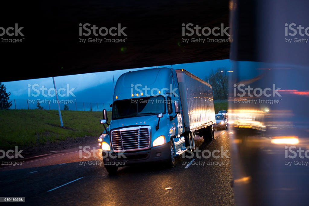 Bright semi truck in raining night lights on highway stock photo