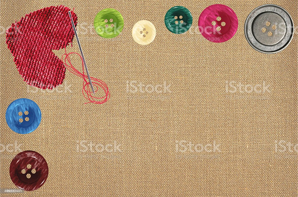 Bright sewing buttons, red textile heart and needle on fabric royalty-free stock photo