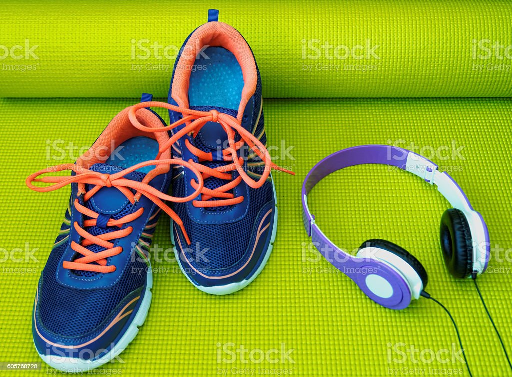 Bright Shoes and Headphones on Rolled Yoga Mat stock photo