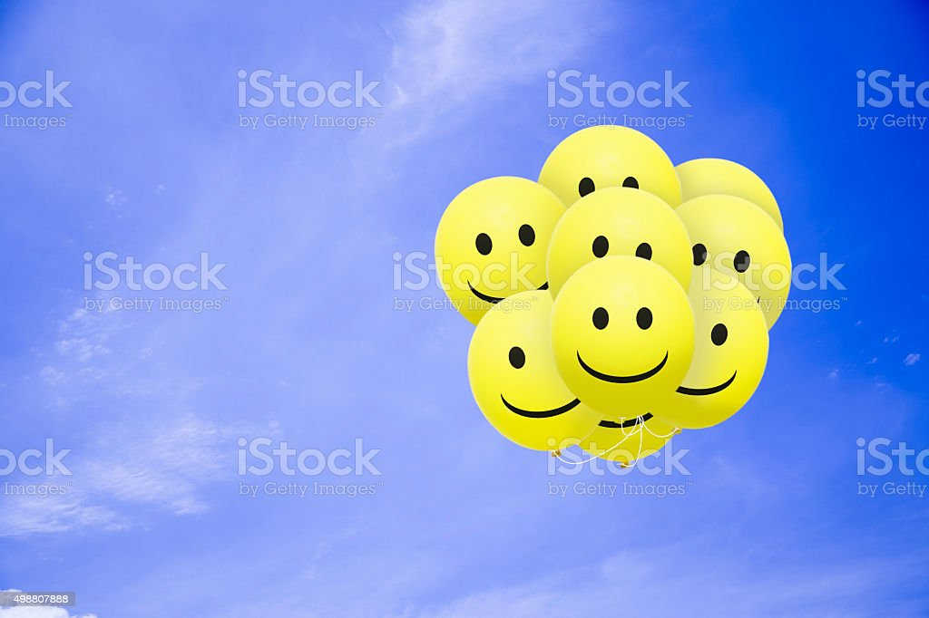 Bright smile balloons flying in the blue sky stock photo