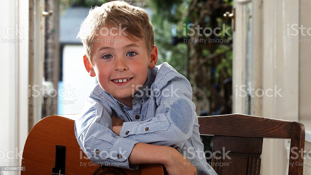 Bright smile from boy with guitar stock photo