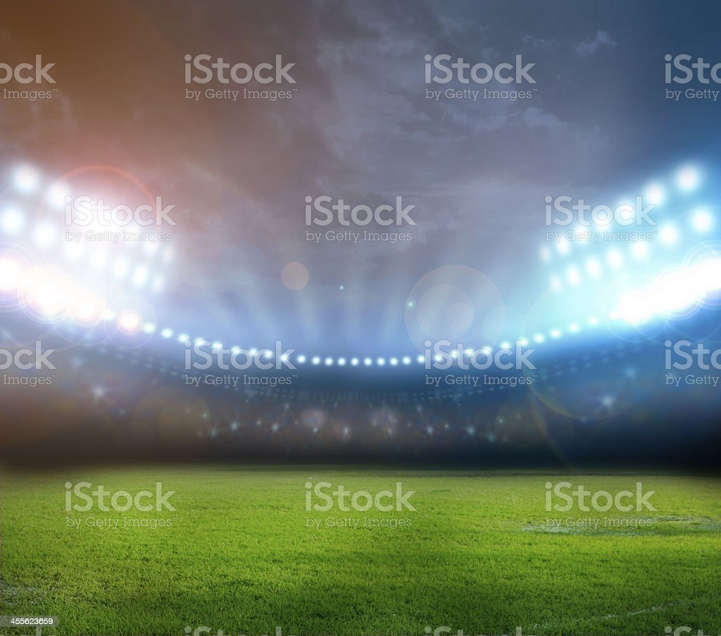Bright stadium lights illuminating field at night stock photo