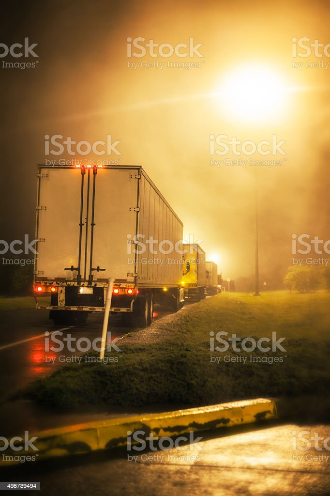 Bright Street Lamps Above Parked Night Time Trailer Trucks stock photo